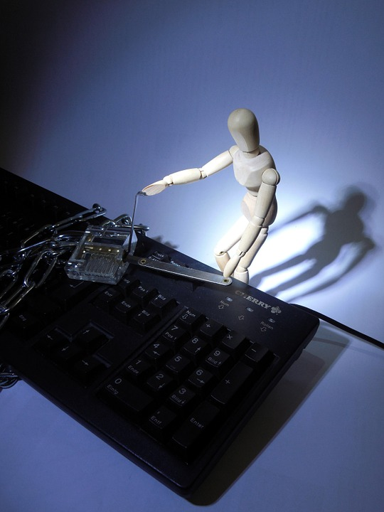 A pose reference doll picking a lock on top of a keyboard