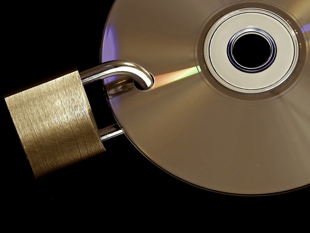 A CD with a padlock through a hole in it.