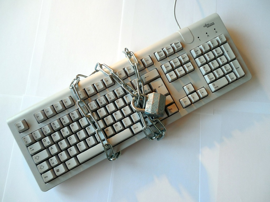 A Keyboard with a locked chain wrapped around it.