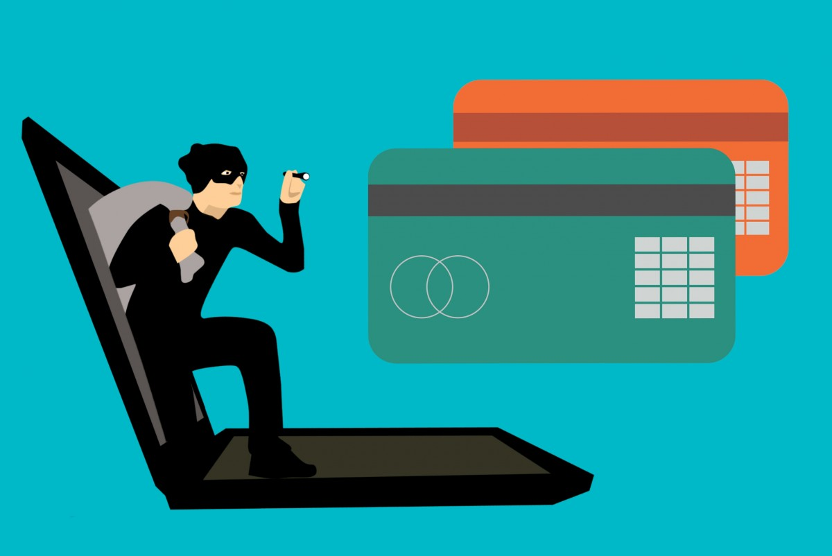 A thief climbing out of a laptop, shining a small flashlight on two oversized credit cards.