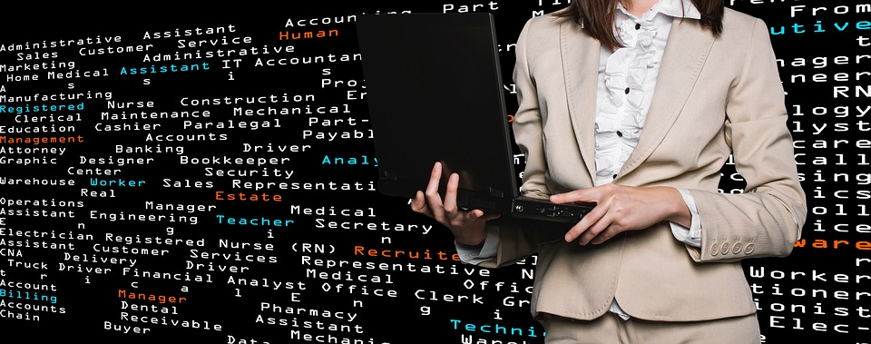 A faceless business woman, holding a laptop, standing in front of a wall of misc. code.
