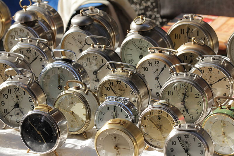 A large number of mechanical alarm clocks arranged on a table together.